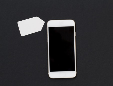 White phone with blank price label on black background. Smartphone with black screen banner template. Mobile phone and discount tag. Flat lay composition with cartoon label cut out from white paper