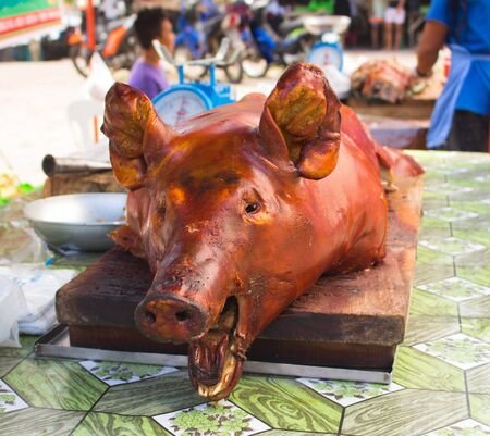 pinoy: Roasted pigs head on markets table in sunlight. Tasty meat lunch photo. Whole pork grilled. Traditional Philippines dish. Pinoy lechon image. Outdoor eatery food. Meat delicatessen - grilled pork Stock Photo