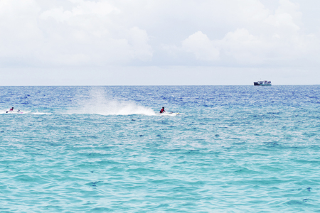 seawater: Seawater landscape with cargo ship on horizon and speedboat. Sea view of boats and sailors. Motor boats race in sea. Marine racing championship. High speed motorboat sail. Sea water spray. Water sport Stock Photo