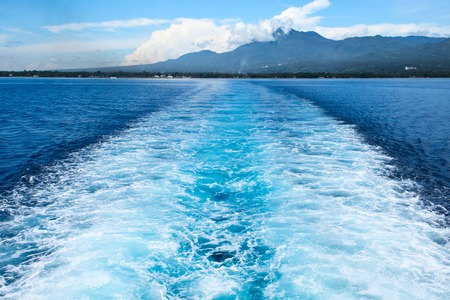 pitching: Sea ship tail and island landscape. Tropical islands ferry travel. Cruiseliner seawater trail. Deep ocean top view. Big ship pitching image. White water wave in the sea. Exotic island hopping
