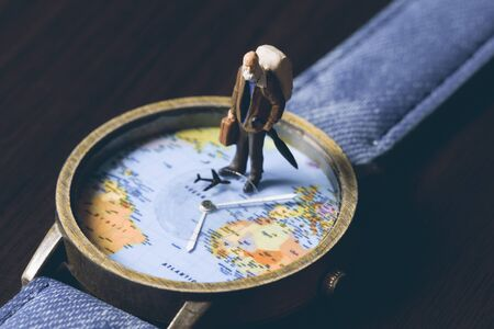 Old man on watches with world map, vintage toned photo. World travel banner. Senior traveler figurine. World time zones. Travelling around world concept. Senior age travel. Time of life in vacation Stock Photo