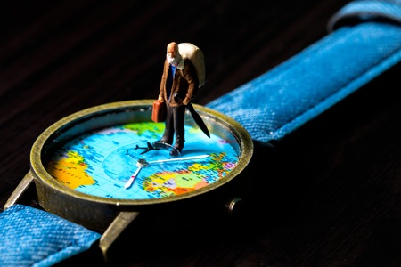 Aged man and world map travel watches. World travel photo banner. Senior traveler figurine. Retired backpacker travel. World time zone. Travelling around world concept. Senior age travel. Time of life