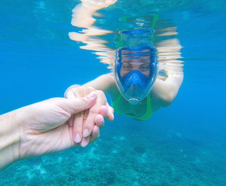 Snorkeling woman in full-face snorkeling mask. Swimming girl holds hand of partner. Romantic underwater photo. Snorkeling lesson. Sea water sport. Coral reef snorkeling. Swimming woman guiding by hand Stock Photo