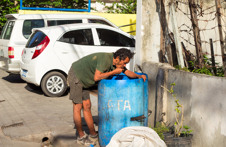Dumaguete, Philippines - 6 August, 2017: Homeless man seek food in garbage by car parking. Economic problem poverty concept. South Asia social unprotected people. Poor hungry beggar eats by trash bin Editorial