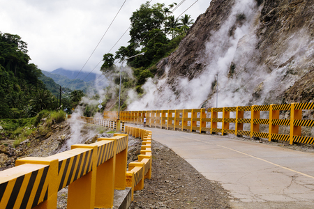 unsafe: Steaming mountains and highway with orange borders. Natural boiling water in hot springs. Serpentine road in mountains. Volcanic island relief. Geothermal spring. Steaming rocks. Volcano eruption risk Stock Photo