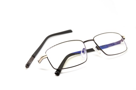 Broken glasses on white background. Eye glasseswith thin metal rim after accident. Computer glasses with broken ear. Optic repair concept. Unisex eyewear isolated. Fragile eyeglasses misuse and fix