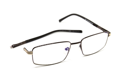 Broken optic glasses on white background. Eye glasseswith thin metal rim after accident. Computer glasses with broken ear. Optic repair concept. Unisex eyewear isolated. Elder age vision healthcare