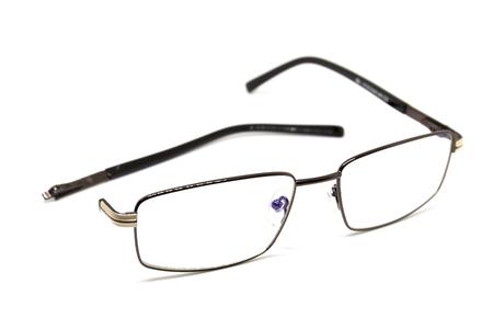Vidrios ópticos quebrados en el fondo blanco. Eye glasseswith thin metal rim after accident. Gafas de computadora con la oreja rota. Concepto de reparación óptica. Gafas unisex aisladas. El cuidado de la visión de la ancianidad Foto de archivo - 87837901