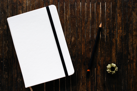 White cover sketchbook with black pencil on rustic wooden table flat lay photo. Closed notebook with blank cover flat lay photo. Notepad on table top view. Notebook banner template.