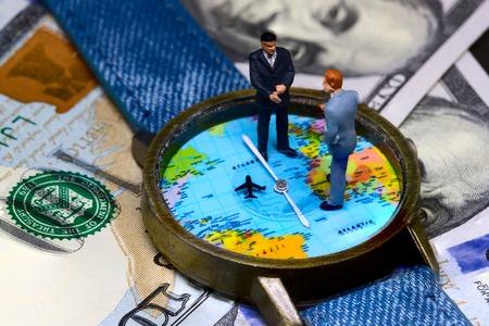 Zwei Geschäftsmannfigürchen auf Zeit- und Geldhintergrund. Weltweites Geschäftskonzept. Internationales Geschäftsabkommen. Strategische Partnerschaft eines globalen Unternehmens. Globaler Geschäftsgewinn. Globaler Markt
