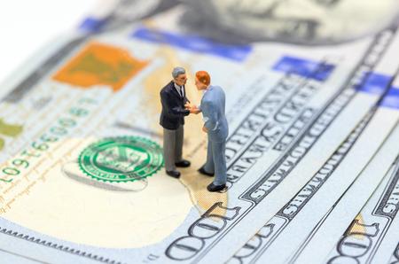 Zakenlieden die handen op Amerikaanse dollar schudden. Zakenliedenbeeldjes op geldachtergrond. Financiële groei. Bedrijfs winst of inkomen concept. Koop en verkoop transacties voor contant geld. Corruptie betaling Stockfoto