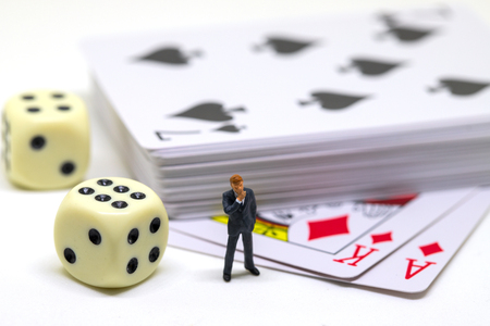 Businessman figure and table game accessories. Poker with dice. Poker hand. Gambling game and player. Table game with card desk and dice. Cheating in card game. Winning strategy or luck. Chance to win Stock Photo