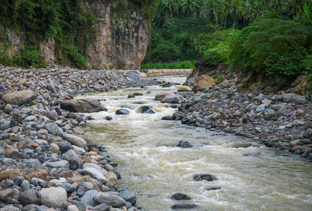 Mountain river with stones. Tropical landscape. Fresh river in stone riverbed. Tropical nature in rain season. Jungle bush view. Thailand rafting. Summer travel adventure. Ecotourism and trekking