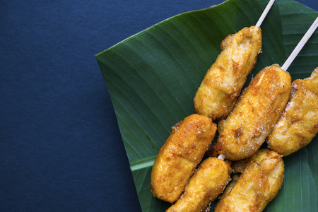 Fried banana on banana leaf plate. Filipino dessert banana cue. Golden banana on stick served for food. Tropical resort breakfast. Exotic island lifestyle. Tropical dessert. South Asia dish flat lay