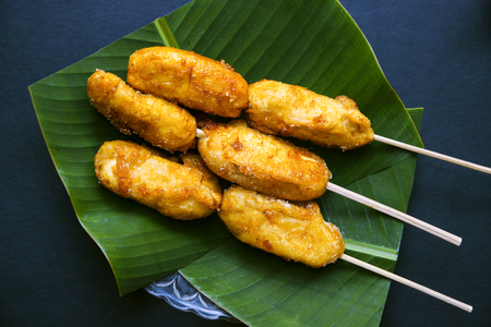 Fried banana on banana leaf plate toned photo. Eastern dessert. Golden banana on stick served for food. Tropical resort breakfast. Exotic island lifestyle. Tropical dessert. Asian streetfood flat lay