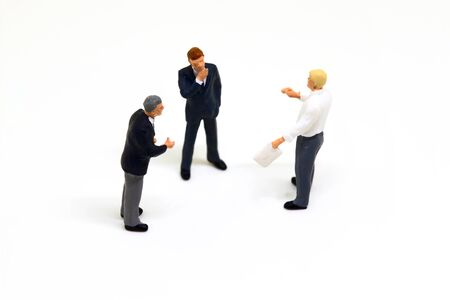 Miniature businessman on white background. Business men figurines macro photo. Businessmen meeting and presentation. Effective communication. Competition and cooperation concept. Executive managers