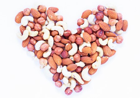 Nut heart on white background. Almond, cashew, hazelnut nuts. Organic food rustic banner template. Tasty healthy snack. Scattered nut on table top view. Nut assortment flat lay. Valentine nut ornament Banco de Imagens