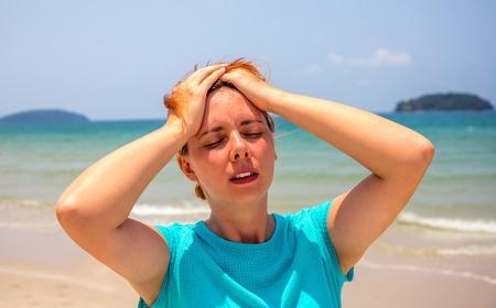 Vrouw aan zee met zonnesteek. Gezondheidsprobleem op vakantie. Geneeskunde op vakantie. Gevaarlijke zon. Strand dag. Zonnesteek op heet strand. Meisje onder de zon. Ongezond meisje op strand over zee. Vakantie gezondheidszorg Stockfoto