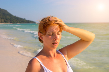 Woman having sun stroke on sunny beach. Woman on hot beach with sunstroke. Health problem on holiday. Medicine on vacation. Dangerous sun. Beach life. Sunstroke on sunny beach. Healthcare in tropics Stock Photo