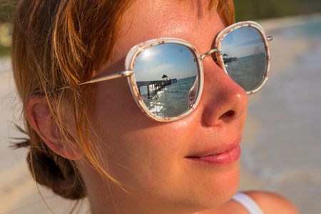 Woman's face in mirror sunglasses with sea reflection. Seaside vacation banner template. Smiling girl in sunglasses by tropical beach. Tropical sea landscape with relaxed girl. Summer holiday photo Zdjęcie Seryjne