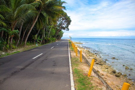 Empty coastal road by the sea. Tropical island holiday travel. Sunny road in tropical nature. Summer travel on car or motorbike. Philippines transportation infrastructure. Blue sky and coco palm trees