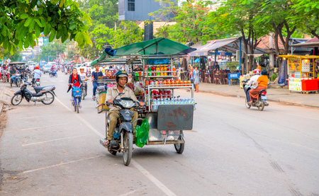 Siem Reap, Cambodia - 31 March 2018: Seller on a motorcycle in the city street. Mobile eatery on bike. Food stall on motorbike. Street eatery on wheels. Low-qualifies asian job. Low-paid asian work