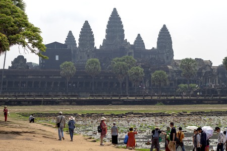 Siem Reap, Cambodia - 25 March 2018: tourists in ancient temple of Angkor Wat complex. Angkor morning view. Popular tourism destination place. Travel and sightseeing in Cambodian place of interest