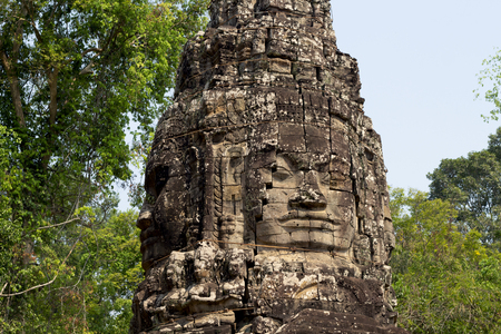 Carved tower bas-relief of Angkor Wat complex temple, Siem Reap, Cambodia. Ancient khmer architecture. Angkor Wat temple archaeological site. Asian tourism sightseeing. Buddha face stone carving