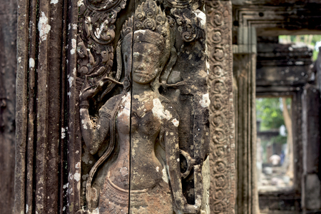 Carved devata bas-relief of Angkor Wat complex temple, Siem Reap, Cambodia. Historical site of khmer architecture. Archaeological place of interest. Tourist sightseeing. Woman figure stone carving