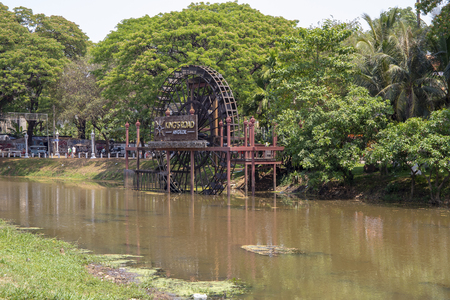 Siem Reap, Cambodia - 25 March 2018: water mill wheel on river. Historical place in Cambodia. Watermill wheel on green river. Rustic lifestyle of khmer people. Countryside landscape and watermill Editorial