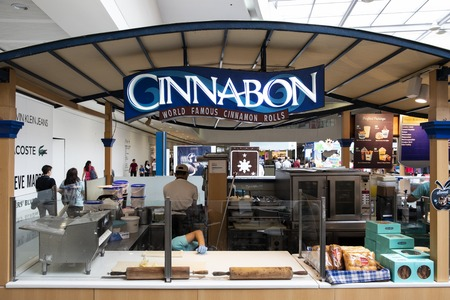 Manila, 22 March 2018 - Cinnabon shop in SM Mall of Asia shopping mall. Cinnamon roll in fast food corner. Food court of shopping mall. Sweet bakery brand name on store front. Famous bakeshop chain