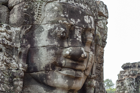Stone face relief of ancient buddhist temple Bayon in Angkor Wat complex, Cambodia.