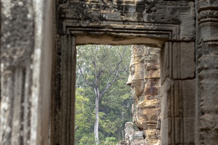 Stone carved face of ancient buddhist temple Bayon in Angkor Wat complex, Cambodia. Фото со стока