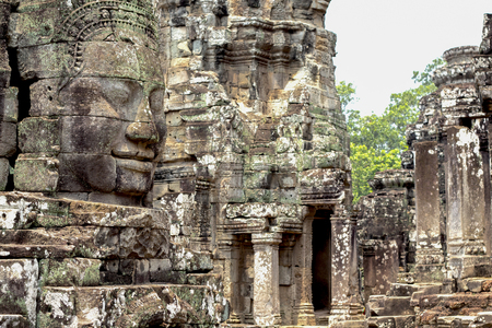 Carved stone face of ancient buddhist temple Bayon in Angkor Wat complex, Cambodia. Фото со стока