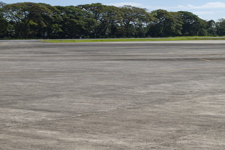 Airport field with greenery. Empty airstrip in tropical country. Summer vacation travel destination. Asphalt field with green trees on background. Grey concrete path with yellow marks. Sunny airfield