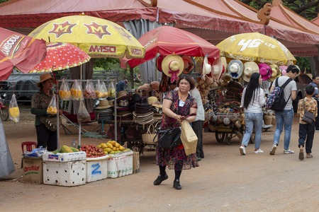 Siem Reap, Cambodia - 14 April 2018: Woman buys food on open fruit market. Cambodian chinese tourist near Angkor Wat. Souvenir and food market. Cambodian tourism business. Public market for tourist