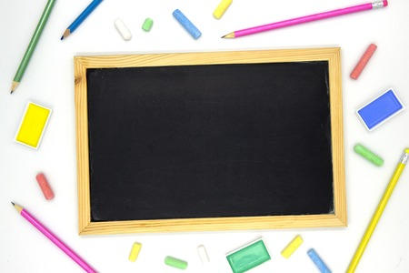 Blank chalkboard in wooden frame with art supplies on white background. Blackboard flat lay photo. School supplies banner template with text place. School year beginning. Chalk board top view mockup