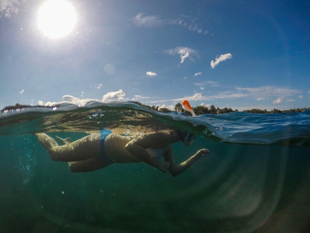 Snorkeling girl in full-face snorkeling mask. Split landscape above and below waterline. Active vacation on seaside underwater photo