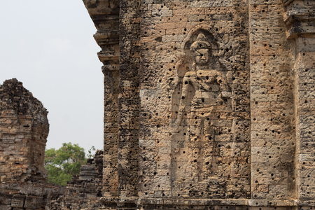 Ancient temple in Angkor Wat complex. Buddhist temple Pre Rup with stone carving bas-relief human figure.