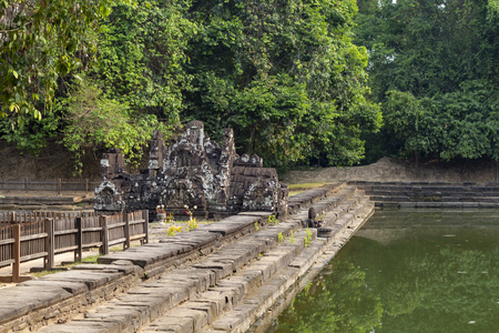 Ancient temple in tropical landscape, Angkor Wat complex. Buddhist or hindu temple Neak Pean with pond and trees.
