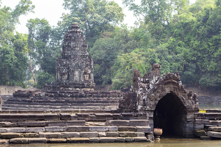 Ancient temple in Angkor Wat complex. Ancient stone temple Neak Pean in green tropical landscape.