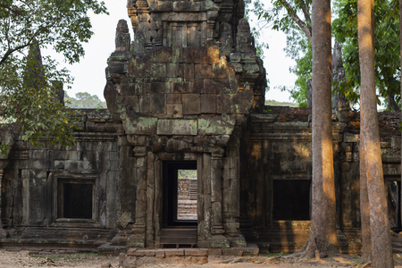 Ancient temple in Angkor Wat. Angkor Thom stone wall remains and trees. Buddhist or hindu temple. Khmer architecture heritage.