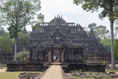 Tourist man in Angkor Wat temple ruin. Ancient temple Baphuon stone ruin in green tropical landscape. Khmer architecture heritage.