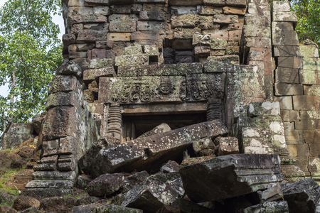 Ancient stone ruin in Angkor Wat temple. Demolished temple with carved bas-relief. Khmer heritage ruin in jungle. Angkor Wat architecture detail. Asia travel photo. Tourism sightseeing in Cambodia