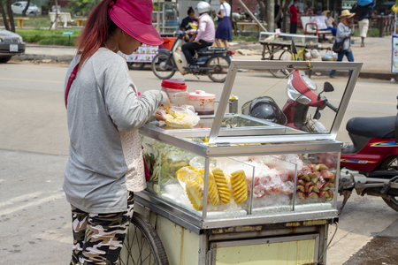 Siem Reap, Cambodia - 26 March, 2018: Young woman sell fruit from mobile stand. Street food seller. Local business and simple job in Asia. Mobile fruit seller. Tropical fruit for sell. Asian lifestyle