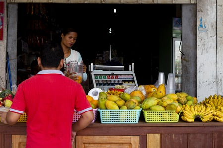 Koh Rong island, Cambodia - 6 April 2018: khmer man buy tropical fruit in local store. Mango and banana on local shop. Buyer and seller by fruit stand. Cambodian people lifestyle. Sweet tropical fruit Editorial