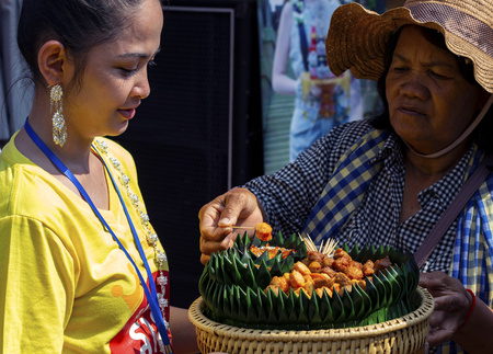 Siem Reap - 14 April 2018: Cambodian promoter girl gives food to try to old woman. Promotional gift small canape. Modern khmer street life. Marketing and advertising. Outdoor festival celebration