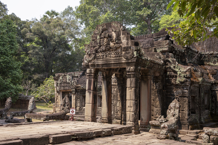 Ancient ruins of Banteay Kdei temple in Angkor Wat complex, Cambodia. Stone bas-relief scene on entrance portal. Abandoned temple in green jungle. Tourism and sightseeing place in Asia.