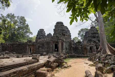 Ancient ruins of Banteay Kdei temple in Angkor Wat complex, Cambodia. Demolished temple view. Old stone temple ruin. Abandoned temple in green jungle. Tourism and sightseeing place in Asia. Фото со стока