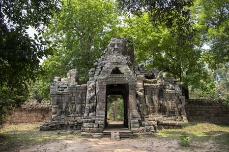 Ancient ruins of Banteay Kdei temple in Angkor Wat complex, Cambodia. Demolished stone tower with Buddha face. Abandoned temple in green jungle. Tourism and sightseeing place in Asia. Фото со стока